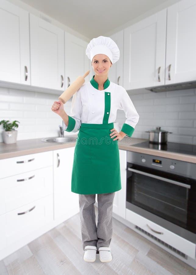 Mulher feliz no uniforme do cozinheiro chefe com o pino do rolo de madeira do cozimento no mo foto de stock