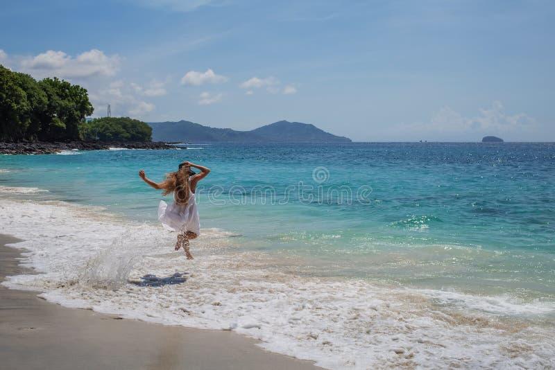 Mulher feliz no vestido branco em f?rias tropicais da praia fotografia de stock