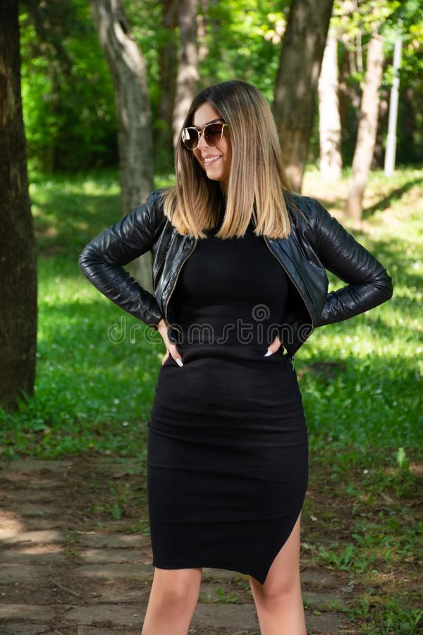 Mulher feliz no vestido preto e casaco de cabedal e óculos de sol que levantam na natureza em um dia de mola ensolarado com mãos  imagem de stock royalty free