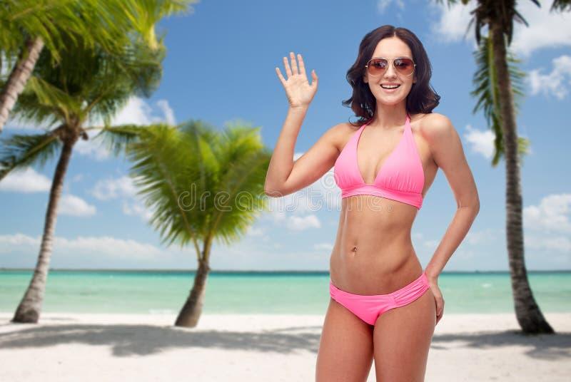 Mulher feliz nos óculos de sol e no biquini na praia foto de stock royalty free