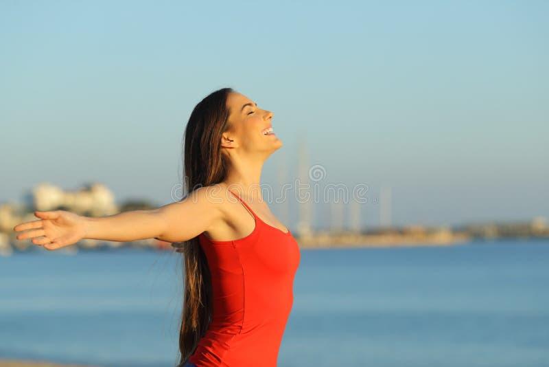 Mulher feliz nos braços outstretching vermelhos na praia fotografia de stock