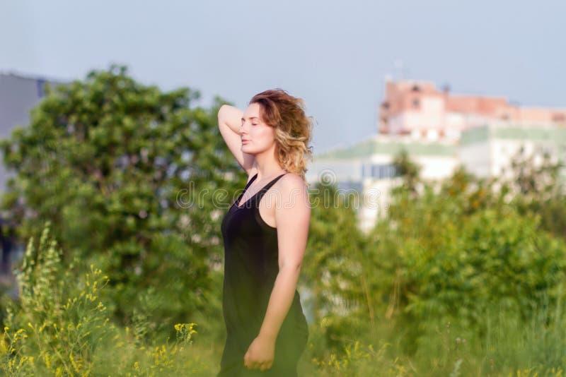 A mulher feliz nova aprecia o sol imagem de stock
