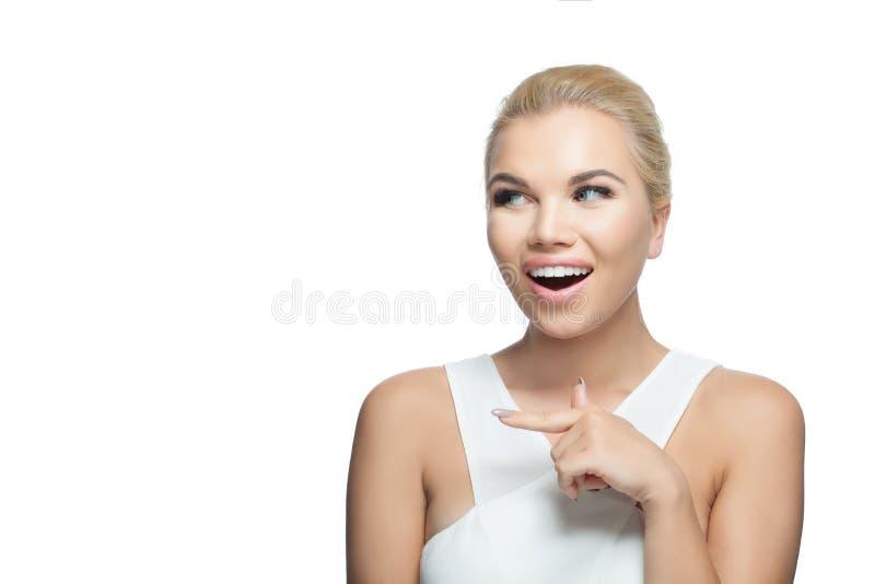 Mulher feliz nova bonita que aponta o dedo isolado no fundo branco Emoção positiva fotografia de stock