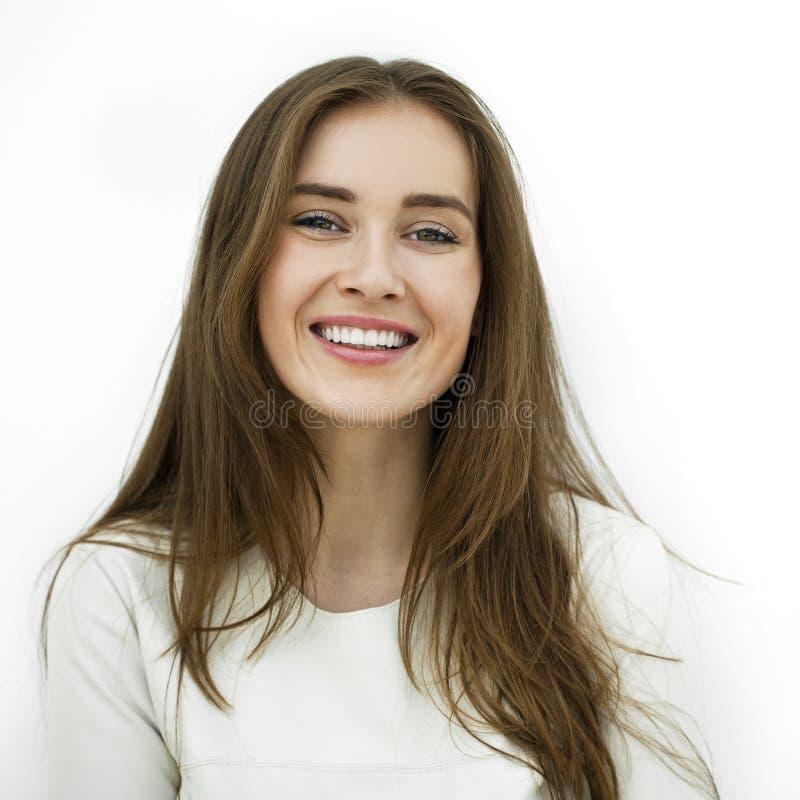 Mulher feliz nova bonita que levanta contra uma parede branca foto de stock