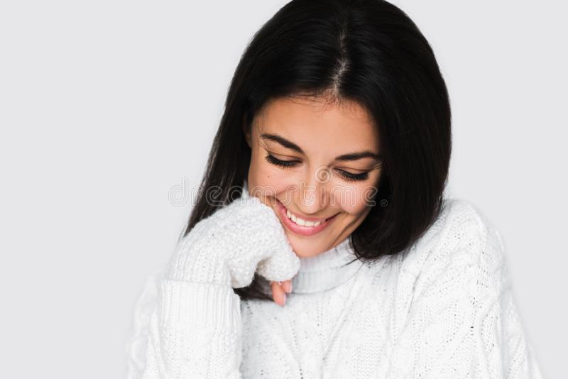 Mulher feliz nova bonita que ri sinceramente com os dentes perfeitos na camiseta branca em claro - fundo cinzento Sorriso triguen fotografia de stock