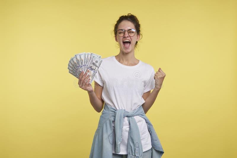 A mulher feliz nova com cabelo encaracolado guarda uns lotes do dinheiro e gritar da felicidade, fotografia de stock