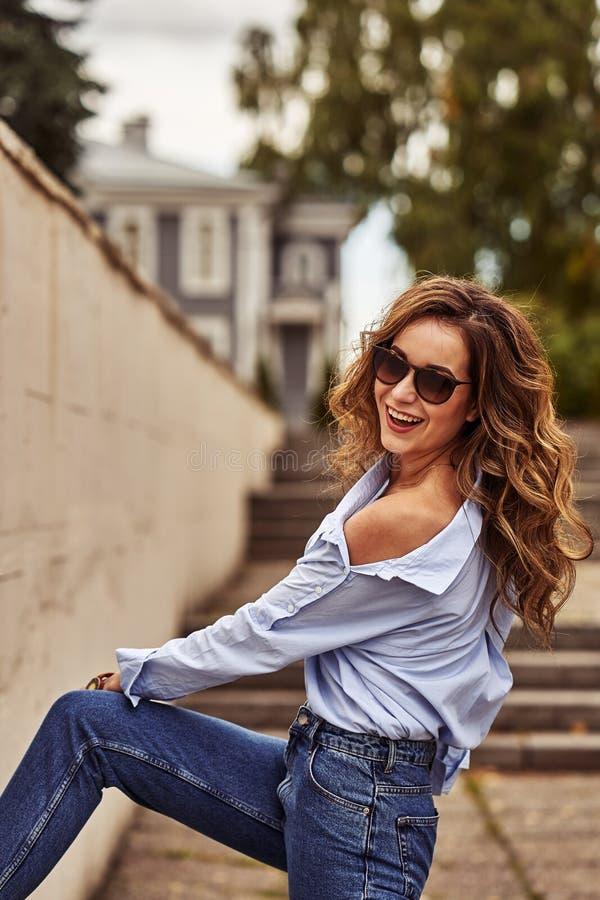 Mulher feliz nova com cabelo marrom longo nos óculos de sol, calças de ganga, caminhadas azuis da camisa através da cidade velha imagem de stock royalty free