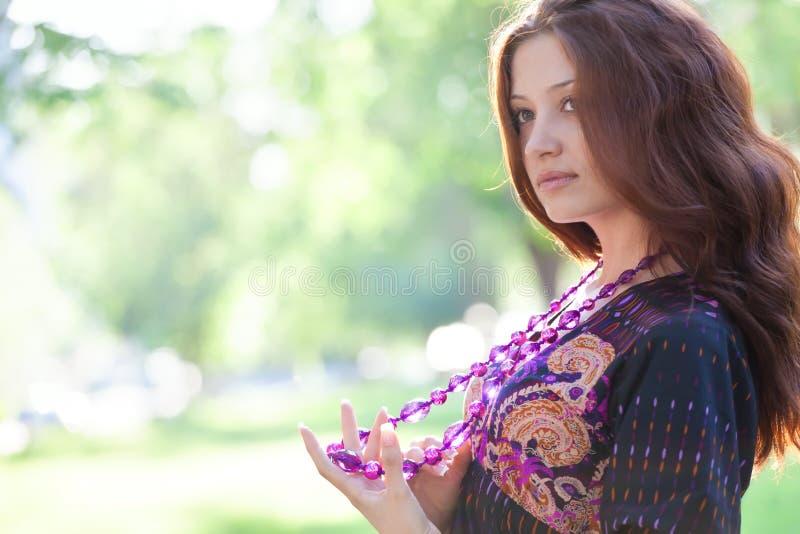 Mulher feliz nova com grânulos roxos foto de stock