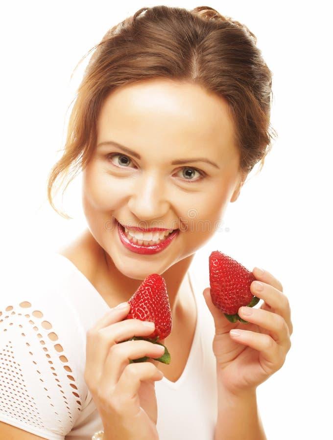 Mulher feliz nova com a morango no fundo branco imagem de stock royalty free