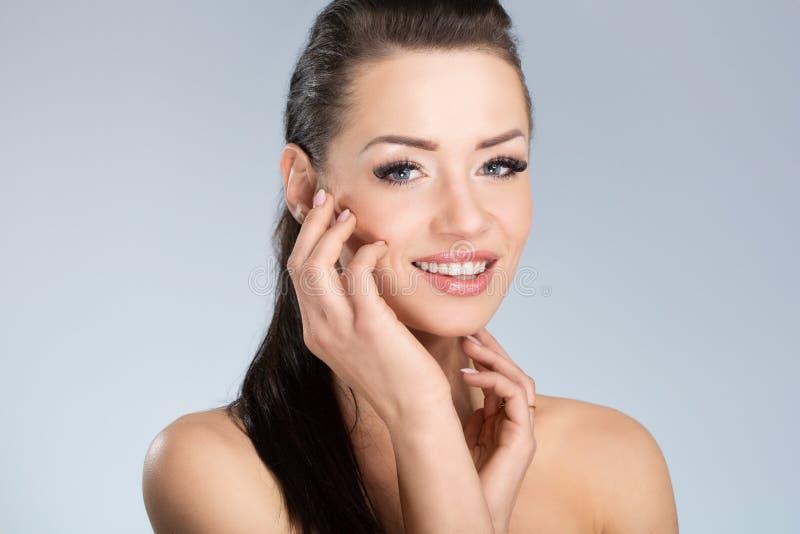 Mulher feliz nova com o cabelo preto que toca em sua cara foto de stock