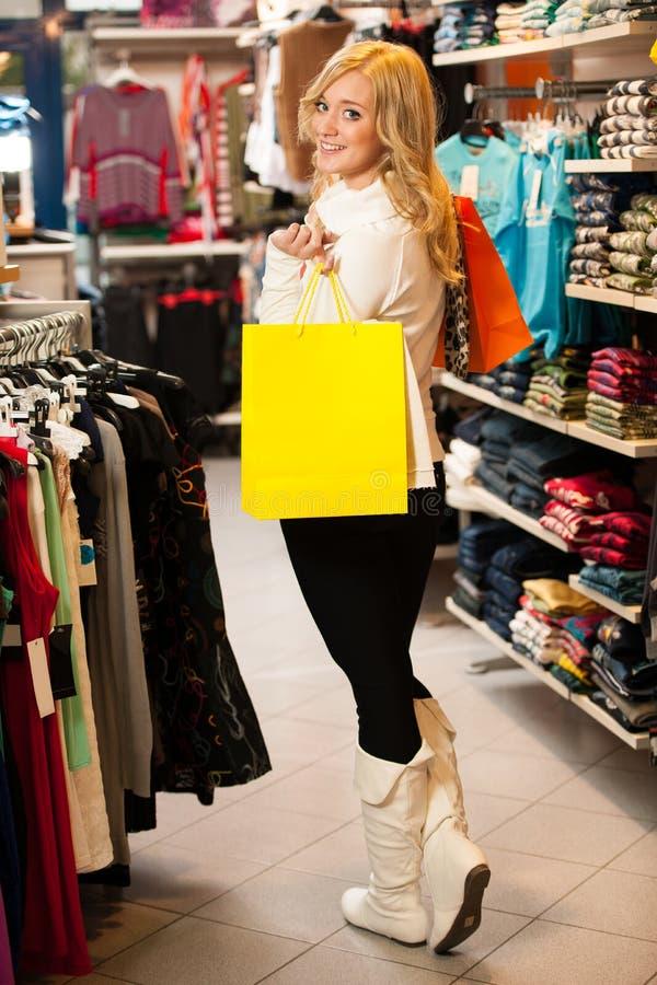Mulher feliz nova com os sacos de compras que saem de um sho imagem de stock royalty free