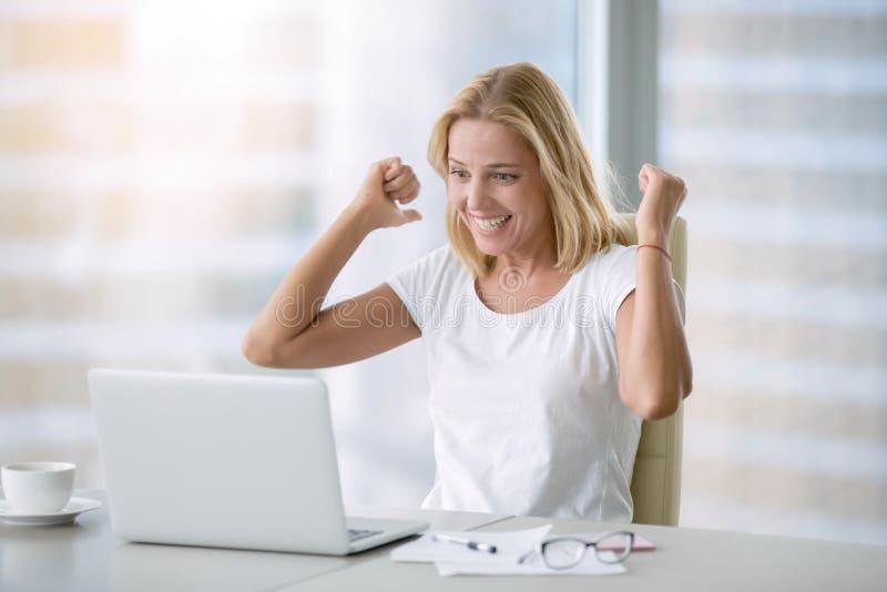 Mulher feliz nova com portátil foto de stock royalty free