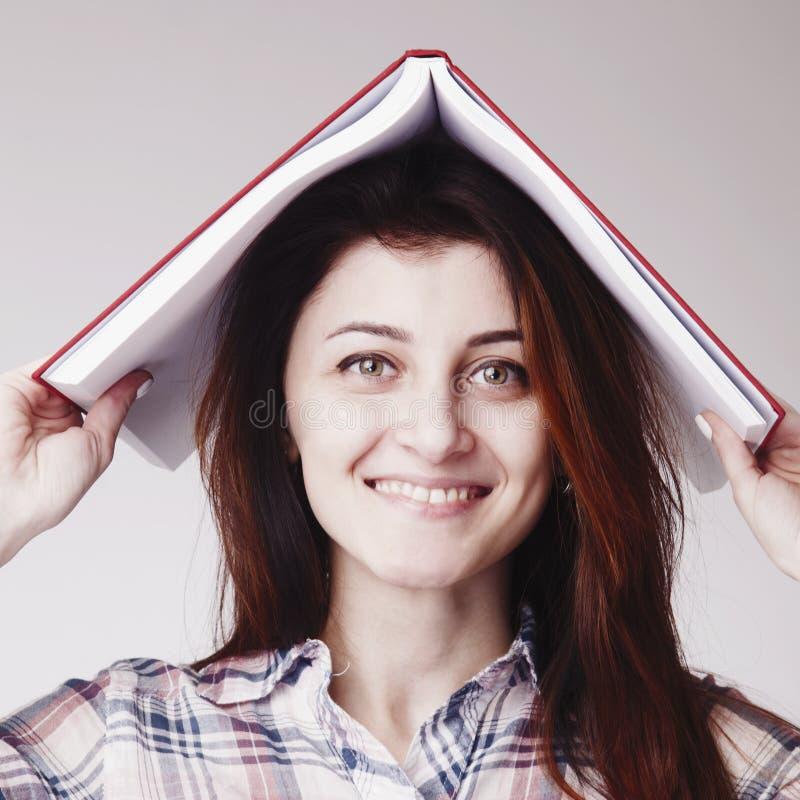 Mulher feliz nova do estudante que guarda livros em sua cabeça como um símbolo fotos de stock royalty free
