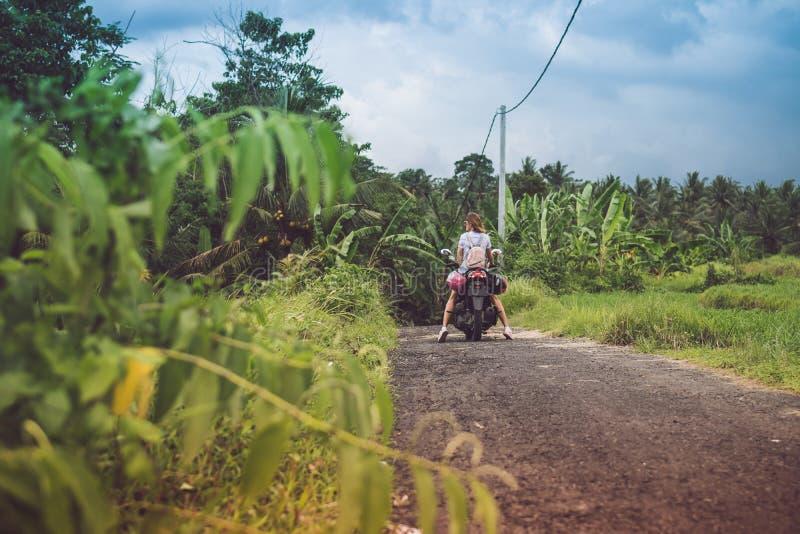 Mulher feliz nova em um velomotor na floresta úmida da selva de uma ilha tropical de Bali, Indonésia Conceito da liberdade Senhor fotos de stock royalty free