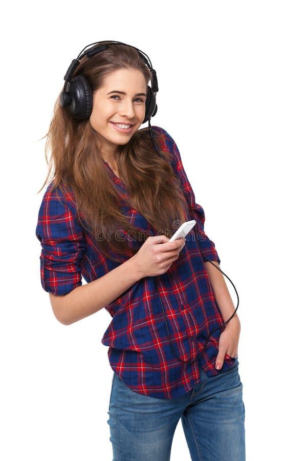 A mulher feliz nova escuta a música isolada no branco imagens de stock