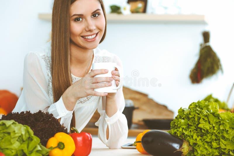 A mulher feliz nova est? guardando o copo branco e est? olhando a c?mera ao sentar-se na tabela de madeira na cozinha entre fotos de stock