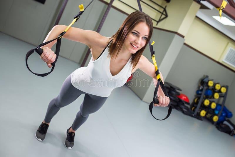 A mulher feliz nova executa flexões de braço Treinamento da suspensão de TRX fotografia de stock royalty free