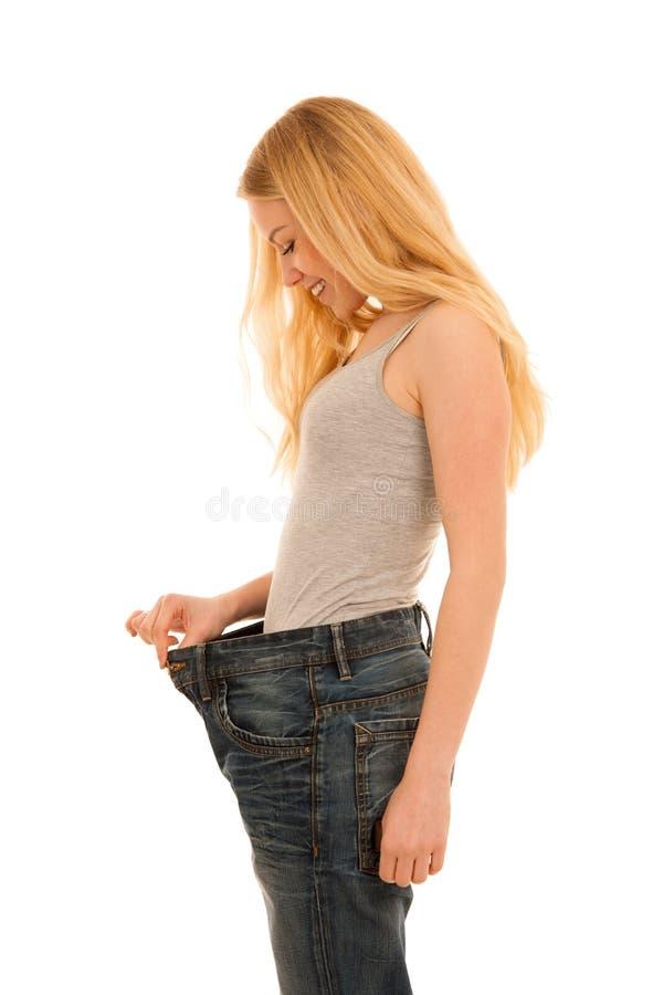 A mulher feliz nova gesticula o sucesso como perdeu muito peso fotos de stock