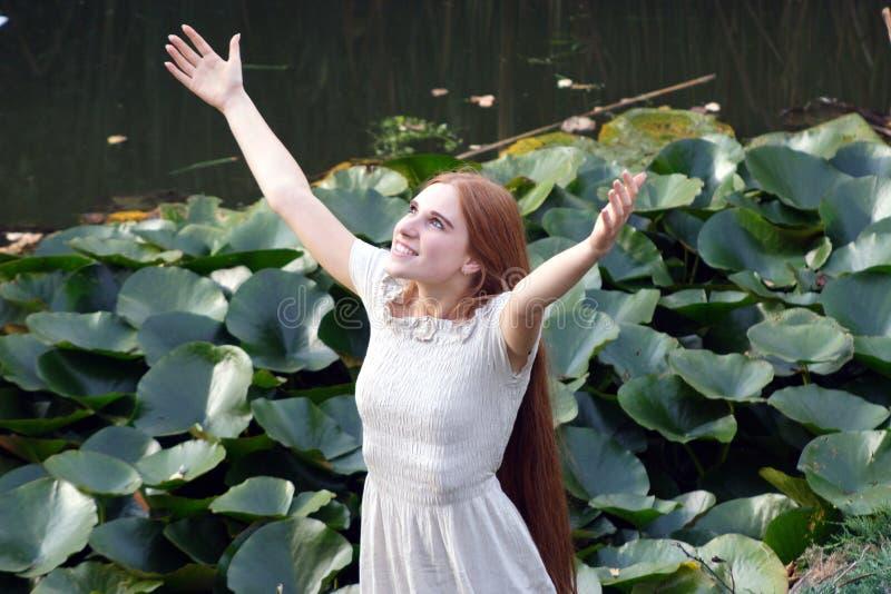 A mulher feliz nova levanta-se as mãos ao céu imagem de stock
