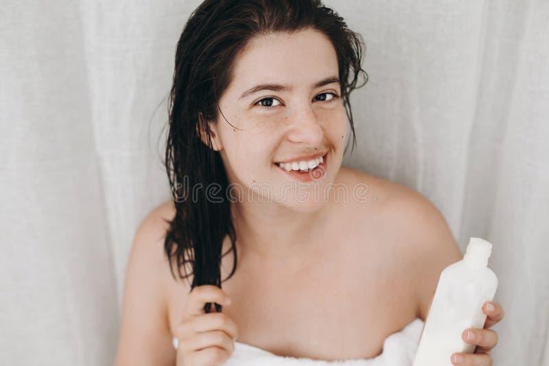 Mulher feliz nova na garrafa branca da terra arrendada de toalha do creme ou do condicionador para o cabelo no banheiro Pele, cor imagem de stock