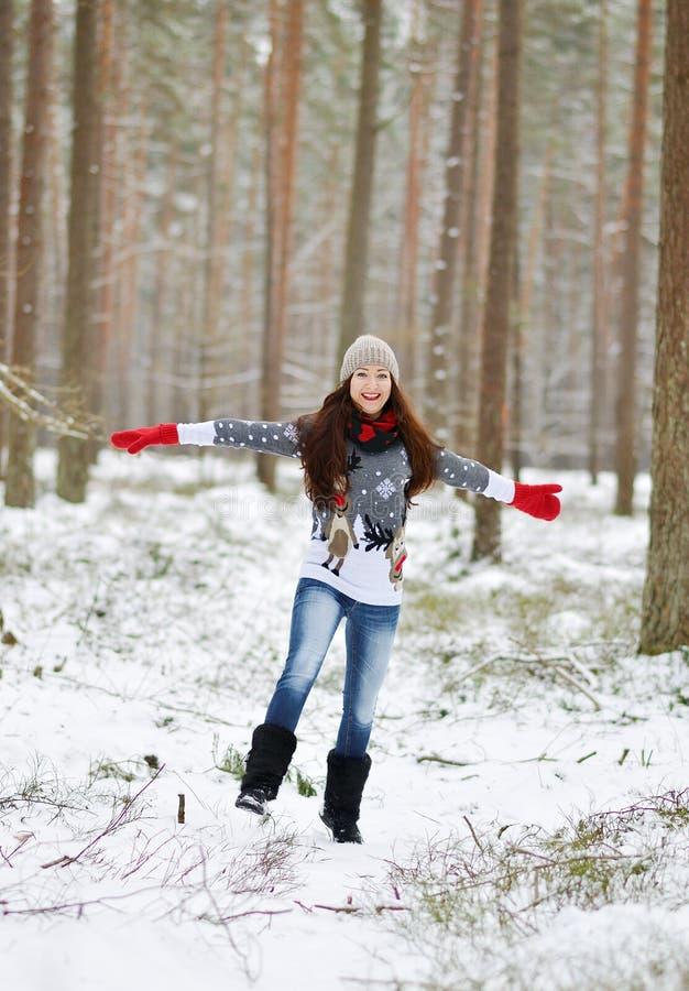 A mulher feliz nova na roupa do inverno anda na floresta nevado imagem de stock