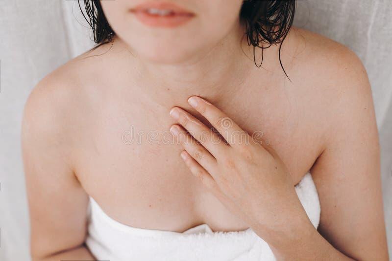 Mulher feliz nova na toalha branca que aplica o creme hidratando no pescoço no banheiro, close up Cuidado da pele e do corpo Mulh foto de stock
