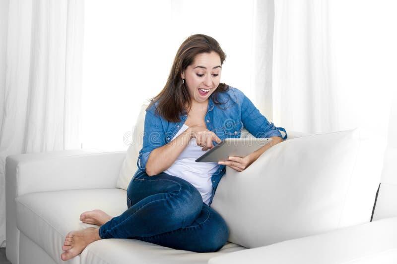 Mulher feliz nova no sofá em casa que aprecia usando o tablet pc digital foto de stock royalty free
