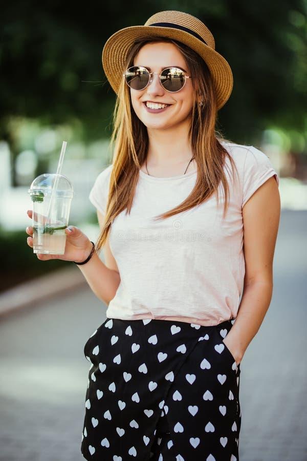 Mulher feliz nova pensativa que sorve um mojito na rua fora imagens de stock