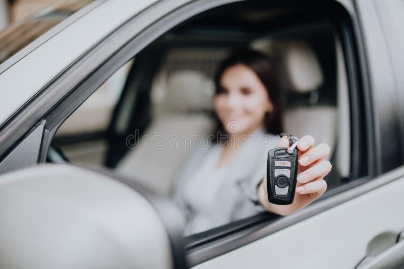 Mulher feliz nova perto do carro com chaves à disposição Conceito do carro de compra Foco na chave fotos de stock