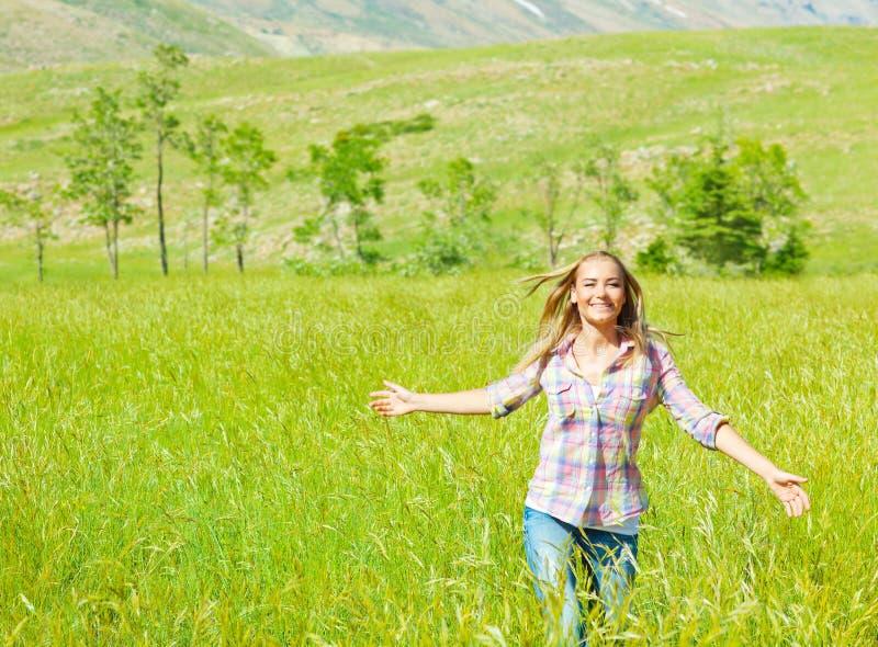 Mulher feliz nova que anda no campo de trigo fotografia de stock royalty free
