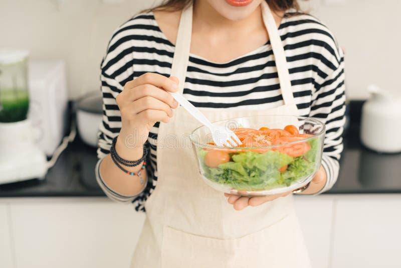 Mulher feliz nova que come a salada Estilo de vida saudável com foo verde fotografia de stock royalty free