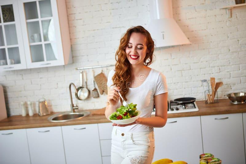 Mulher feliz nova que come a salada na cozinha bonita com os ingredientes frescos verdes dentro Conceito saud?vel do alimento imagens de stock