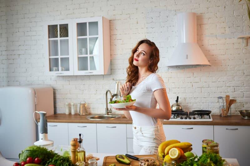 Mulher feliz nova que come a salada na cozinha bonita com os ingredientes frescos verdes dentro Conceito saud?vel do alimento imagem de stock royalty free