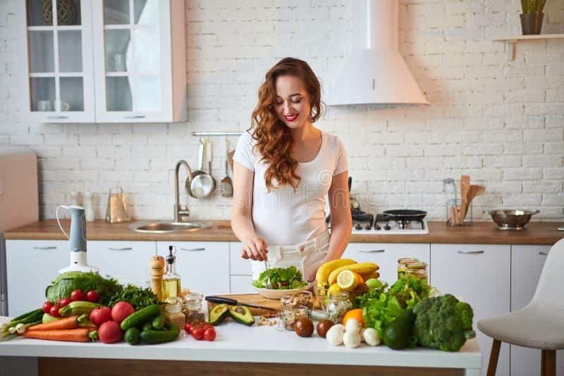 Mulher feliz nova que come a salada na cozinha bonita com os ingredientes frescos verdes dentro Conceito saud?vel do alimento fotos de stock royalty free