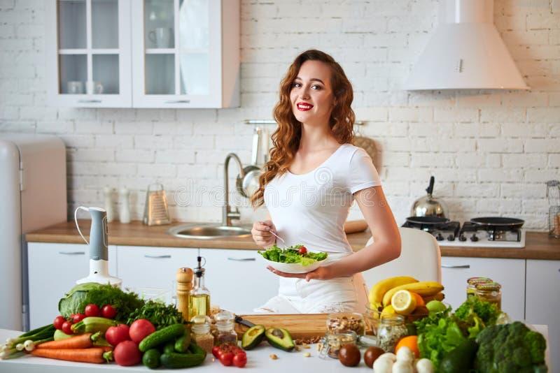 Mulher feliz nova que come a salada na cozinha bonita com os ingredientes frescos verdes dentro Conceito saud?vel do alimento fotos de stock