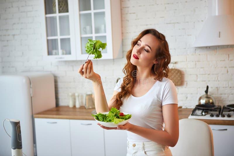 Mulher feliz nova que come a salada na cozinha bonita com os ingredientes frescos verdes dentro Conceito saud?vel do alimento imagem de stock