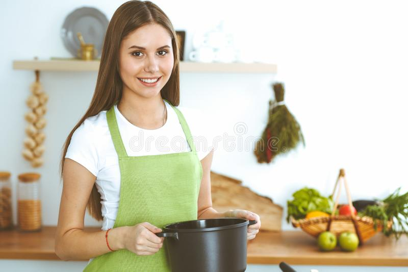 Mulher feliz nova que cozinha a sopa na cozinha Refei??o saud?vel, estilo de vida e conceito culin?rio Menina de sorriso do estud fotografia de stock