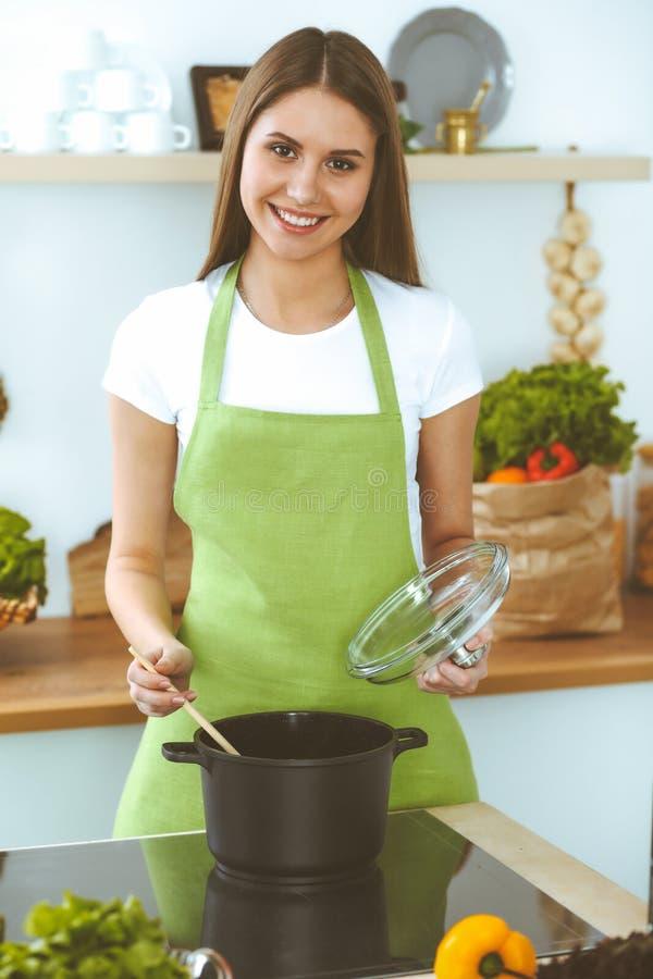 Mulher feliz nova que cozinha a sopa na cozinha Refei??o saud?vel, estilo de vida e conceito culin?rio Menina de sorriso do estud fotografia de stock royalty free