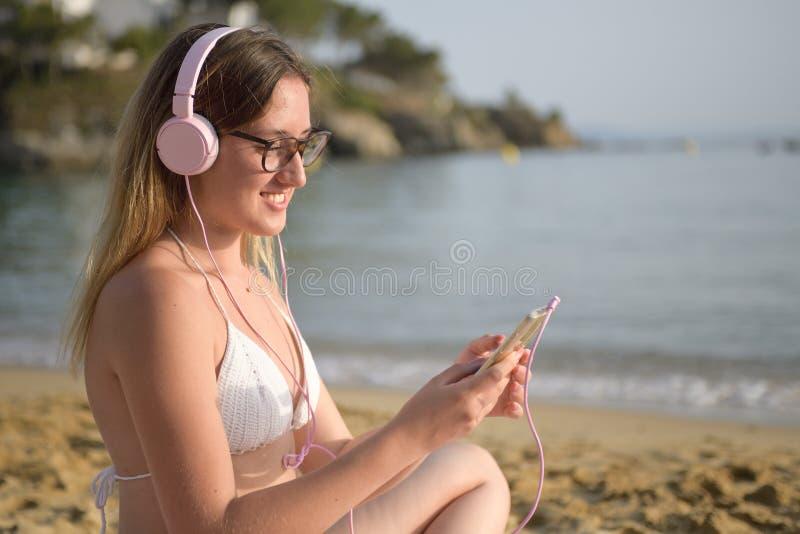 Mulher feliz nova que escolhe músicas na praia imagem de stock