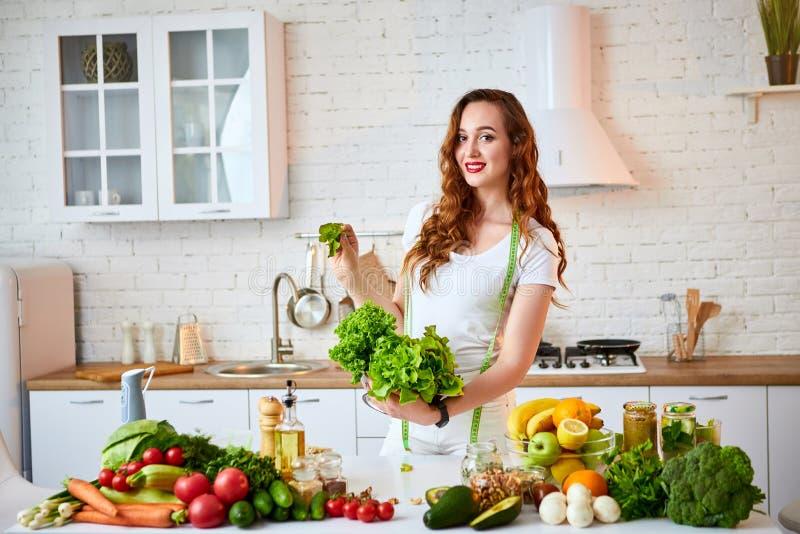 Mulher feliz nova que guarda as folhas da alface para fazer a salada na cozinha bonita com os ingredientes frescos verdes dentro  fotografia de stock royalty free