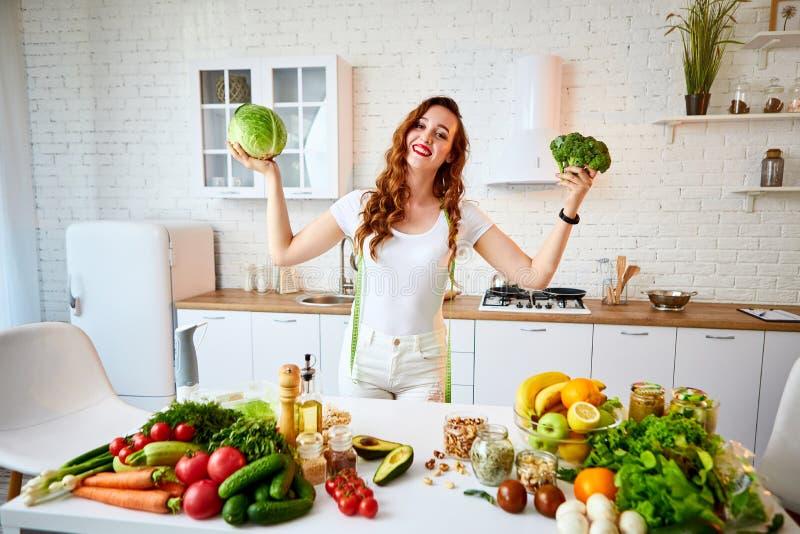 Mulher feliz nova que guarda brócolis e couve na cozinha bonita com os ingredientes frescos verdes dentro alimento saud?vel e foto de stock
