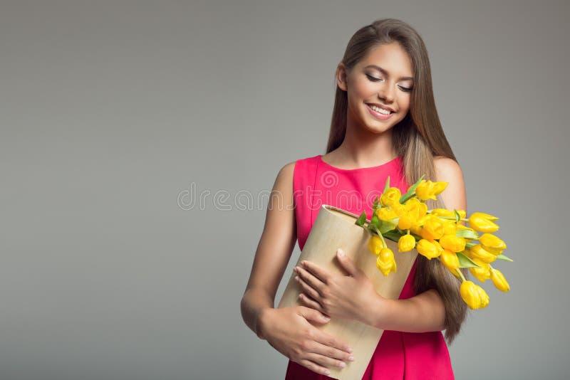 Mulher feliz nova que guarda a cesta com tulipas amarelas fotografia de stock royalty free