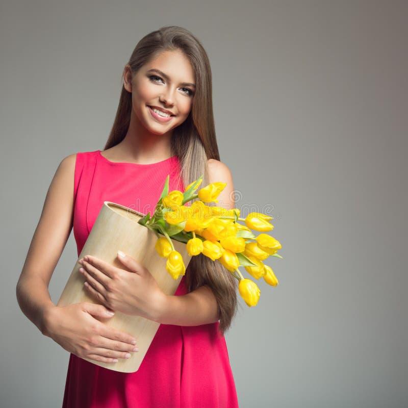 Mulher feliz nova que guarda a cesta com tulipas amarelas fotografia de stock