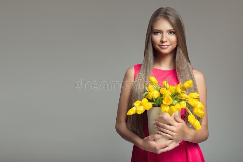 Mulher feliz nova que guarda a cesta com tulipas amarelas Backgr cinzento imagem de stock