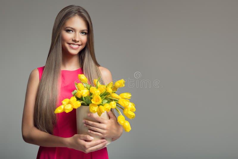 Mulher feliz nova que guarda a cesta com tulipas amarelas Backgr cinzento imagem de stock royalty free