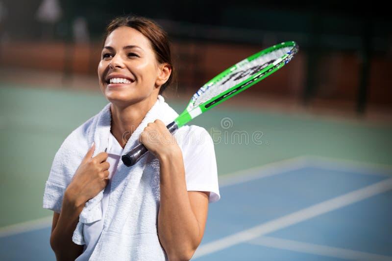 Mulher feliz nova que joga o tênis no campo de tênis fotografia de stock royalty free