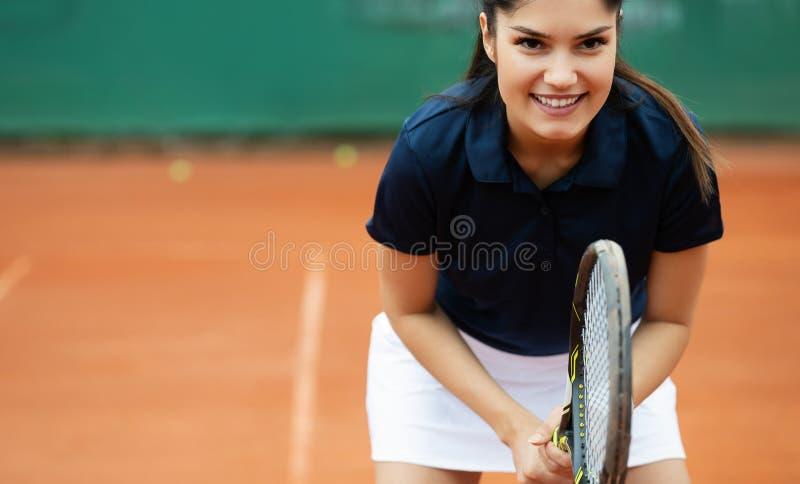 Mulher feliz nova que joga o t?nis no campo de t?nis imagem de stock