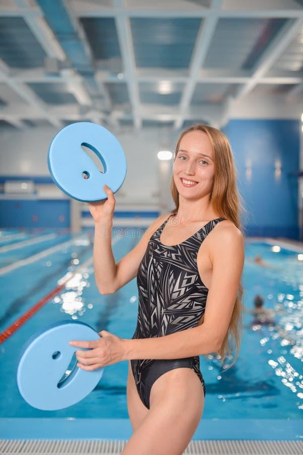 A mulher feliz nova que manipula com flutuação embarca perto da piscina fotos de stock
