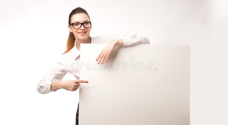 Mulher feliz nova que mostra a apresentação, apontando no cartaz sobre o fundo cinzento foto de stock