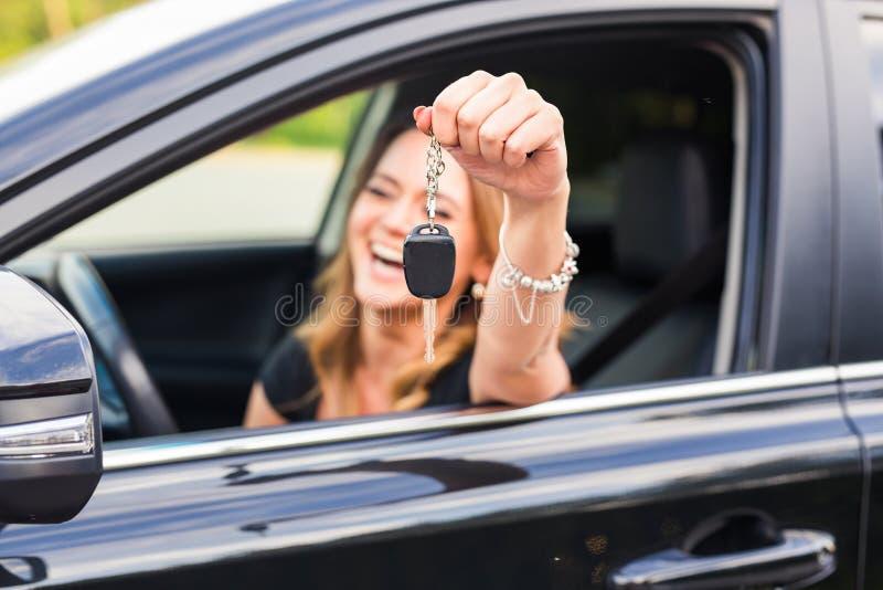 Mulher feliz nova que mostra a chave do carro novo foto de stock